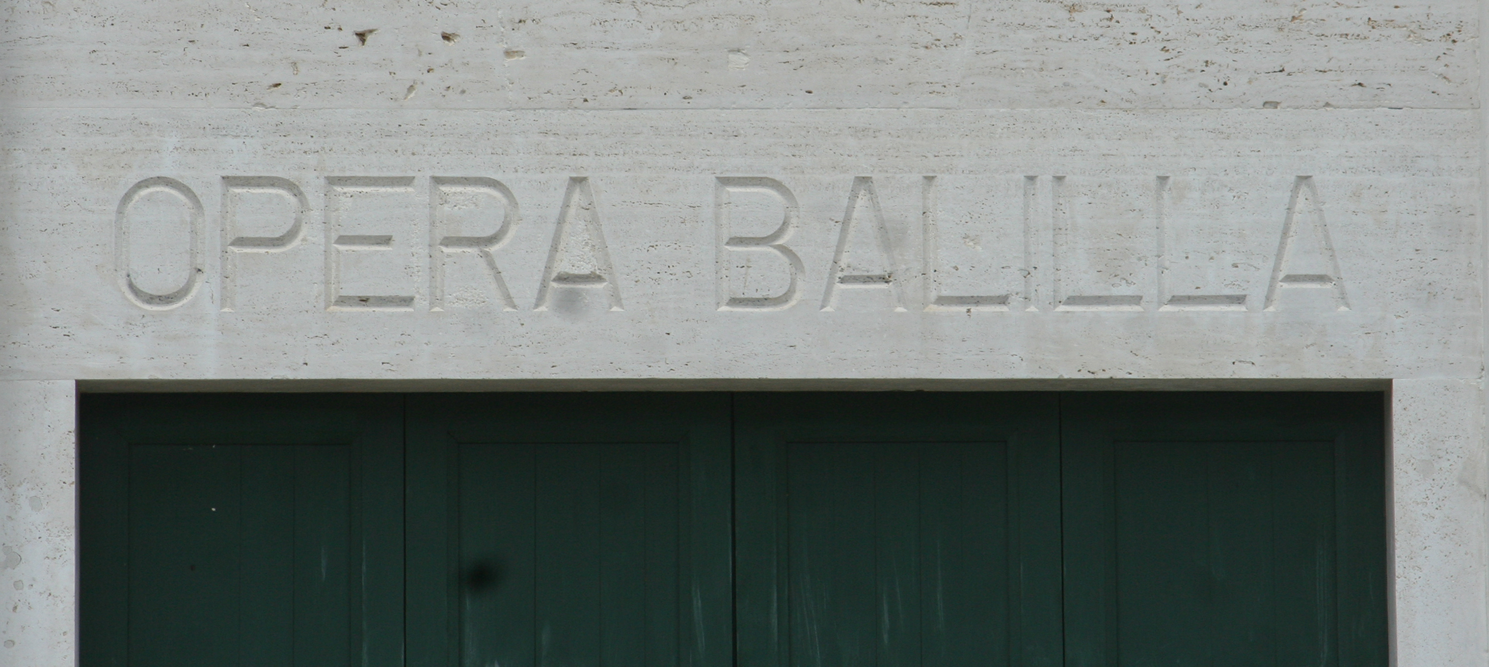 Detail of lettering on the facade of the Opera Balilla (Latina). Latina, established in 1932, was originally named Littoria.
