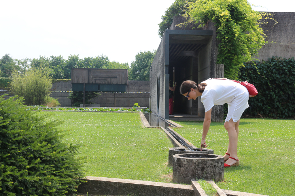 Alta examining the source of the water for the lily pond section of the Tomba Brion by Carlo Scarpa. Photograph by Paul Shaw, 2015.